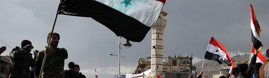 Wafuasi wa Rais Bashar al-Assad wimbi bendera Syria wakati wa mkutano wa hadhara katika al-Sabaa Bahrat mraba katika Dameski