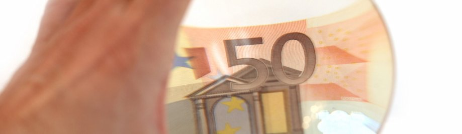hand with the lens. considering the euro banknote